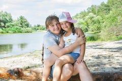 di estate, vicino al fiume, una piccola figlia abbraccia sua madre vicino Fotografia Stock Libera da Diritti