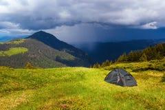 Di fronte ad un'alta montagna verde sta una tenda turistica Immagini Stock Libere da Diritti