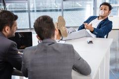Di gomma da masticare di salto dell'uomo d'affari con le gambe sulla tavola durante l'intervista di lavoro Fotografie Stock