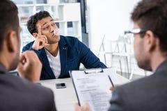 Di gomma da masticare di salto dell'uomo d'affari durante l'intervista di lavoro Fotografia Stock