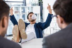 Di gomma da masticare di salto dell'uomo d'affari e mostrare le dita medie durante l'intervista di lavoro Immagine Stock