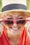 Di gran lunga ritratto degli occhiali da sole d'uso sorridenti della donna senior Immagine Stock