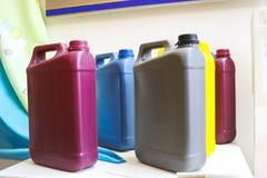 di latte gialle blu grige rosse gialle di plastica colorate Multi con una maniglia per i liquidi, combustibili, oli fotografia stock