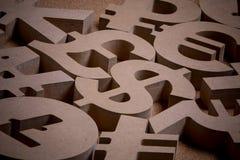Di legno canta o simboli delle valute del mondo nell'immagine del gruppo fotografie stock