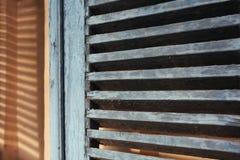 Di legno grigi aprono i ciechi Ombra sulla parete gialla immagini stock libere da diritti