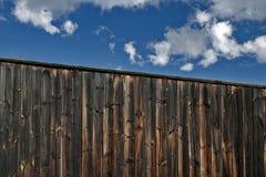 Di legno recinti il giardino con il cielo nuvoloso blu Fotografie Stock