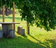 Di mattina in un giardino rustico, in una mobilia di legno e nei rami Fotografia Stock Libera da Diritti