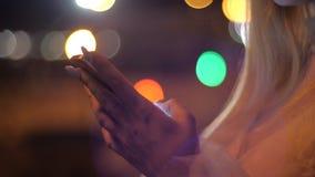 Di notte, una donna bionda con uno smartphone in città Scrivi il messaggio sullo smartphone in città stock footage