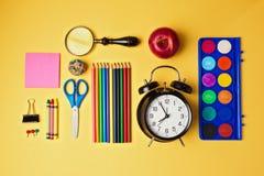 Di nuovo agli oggetti della scuola organizzati su fondo giallo Vista da sopra Fotografia Stock