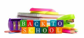 Di nuovo ai blocchetti di legno del giocattolo della scuola con i rifornimenti di scuola fotografia stock