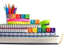 Di nuovo ai blocchetti di legno del giocattolo della scuola sui libri con i rifornimenti di scuola Immagine Stock