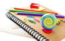 Di nuovo ai rifornimenti di scuola con il taccuino e la matita su backg bianco Fotografia Stock