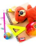 Di nuovo ai rifornimenti di scuola con il taccuino ed il giocattolo dell'orso sul BAC bianco Fotografia Stock