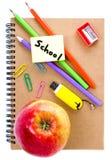 Di nuovo ai rifornimenti di scuola con il taccuino, la mela rossa e la matita sopra Immagine Stock