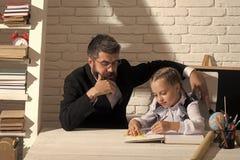 Di nuovo al banco La scolara ed il suo papà con i fronti premurosi scrivono in taccuino Fotografie Stock Libere da Diritti