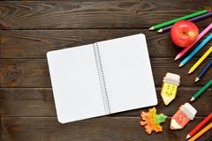 Di nuovo al concetto del banco Apra il taccuino e la mela con le matite colorate, pan di zenzero su fondo di legno Fotografia Stock