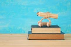 Di nuovo al concetto del banco Automobile di legno del giocattolo con le matite variopinte sul tetto sopra la pila di libri Fotografia Stock
