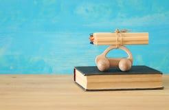 Di nuovo al concetto del banco Automobile di legno del giocattolo con le matite variopinte sul tetto sopra la pila di libro Immagini Stock