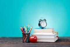 Di nuovo al concetto del banco Libri, matite colorate ed orologio Immagini Stock