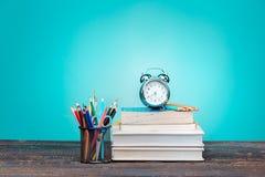 Di nuovo al concetto del banco Libri, matite colorate ed orologio Fotografie Stock Libere da Diritti