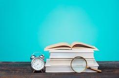 Di nuovo al concetto del banco Libri, matite colorate ed orologio Immagine Stock