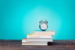 Di nuovo al concetto del banco Libri, matite colorate ed orologio Immagini Stock Libere da Diritti