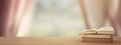 Di nuovo al concetto del banco pila di libri sopra lo scrittorio di legno davanti alla finestra della luce di giorno fotografia stock libera da diritti