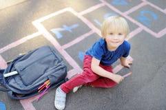 Di nuovo al concetto del banco Ragazzino sul cortile della scuola Fotografia Stock Libera da Diritti