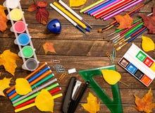 Di nuovo al concetto del banco Rifornimenti di scuola e foglie di autunno su Rus Fotografia Stock Libera da Diritti