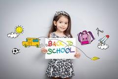 Di nuovo al concetto della scuola: Carta sorridente allegra della tenuta della bambina Fotografia Stock