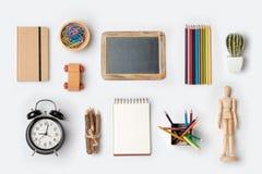 Di nuovo al concetto della scuola con i rifornimenti di scuola organizzati su fondo bianco Immagine Stock