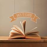 Di nuovo al concetto della scuola con il libro aperto e l'insegna Apra il libro sulla tabella di legno Fotografia Stock