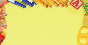 Di nuovo al concetto della scuola: Rifornimenti di scuola su un fondo giallo fotografia stock