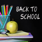 Di nuovo al concetto della scuola. Una mela, le matite colorate ed i vetri sul mucchio dei libri sopra fondo nero Fotografie Stock