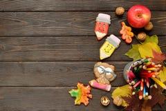Di nuovo al fondo di concetto della scuola con le matite colorate, il appple rosso ed il pan di zenzero sulla tavola di legno Fotografia Stock