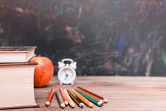 Di nuovo al fondo della scuola con i libri, le matite, l'orologio e la mela su una tavola di legno immagini stock