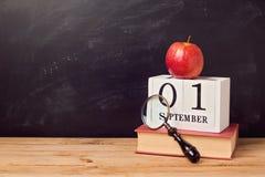 Di nuovo al fondo della scuola con il libro, la mela ed il calendario Fotografia Stock Libera da Diritti