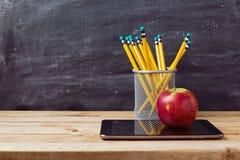 Di nuovo al fondo della scuola con la compressa, le matite e la mela sopra la lavagna Fotografie Stock