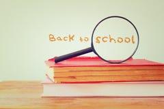 Di nuovo al fondo della scuola con la pila di libri e di lente d'ingrandimento Immagine filtrata Fotografia Stock Libera da Diritti