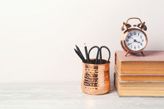 Di nuovo al fondo moderno della scuola con i libri, sveglia fotografia stock