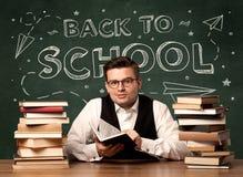 Di nuovo al maestro di scuola che si siede allo scrittorio dell'aula Fotografia Stock Libera da Diritti