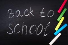 Di nuovo al messaggio della scuola sulla lavagna iscritta con gesso variopinto per fondo Fotografia Stock