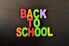 Di nuovo al testo di scuola con ombra su fondo di legno Immagine Stock Libera da Diritti