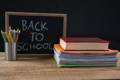 Di nuovo al testo di scuola scritto sulla lavagna con la pila di libro ed il supporto della penna immagine stock libera da diritti