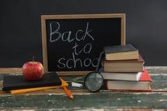 Di nuovo al testo di scuola scritto sulla lavagna con varie cancelleria e mela fotografie stock