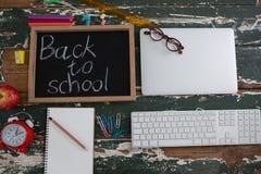 Di nuovo al testo di scuola scritto sulla lavagna con varie cancelleria, mela ed elettronica immagini stock