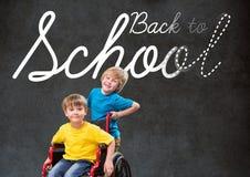 Di nuovo al testo di scuola sulla lavagna con il ragazzo disabile e l'amico in sedia a rotelle Immagine Stock
