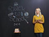 Di nuovo all'insegnante della donna della scuola che sorride dalla lavagna Immagine Stock Libera da Diritti