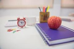 Di nuovo alla mela ed al libro rossi di concetto della scuola sulla tavola bianca Fotografia Stock Libera da Diritti