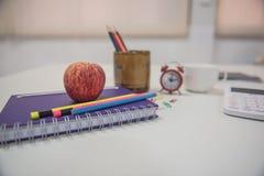 Di nuovo alla mela ed al libro rossi di concetto della scuola sulla tavola bianca Fotografie Stock Libere da Diritti
